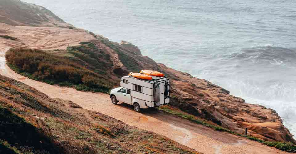white truck camper on the road near the oven after being stored in camper storage