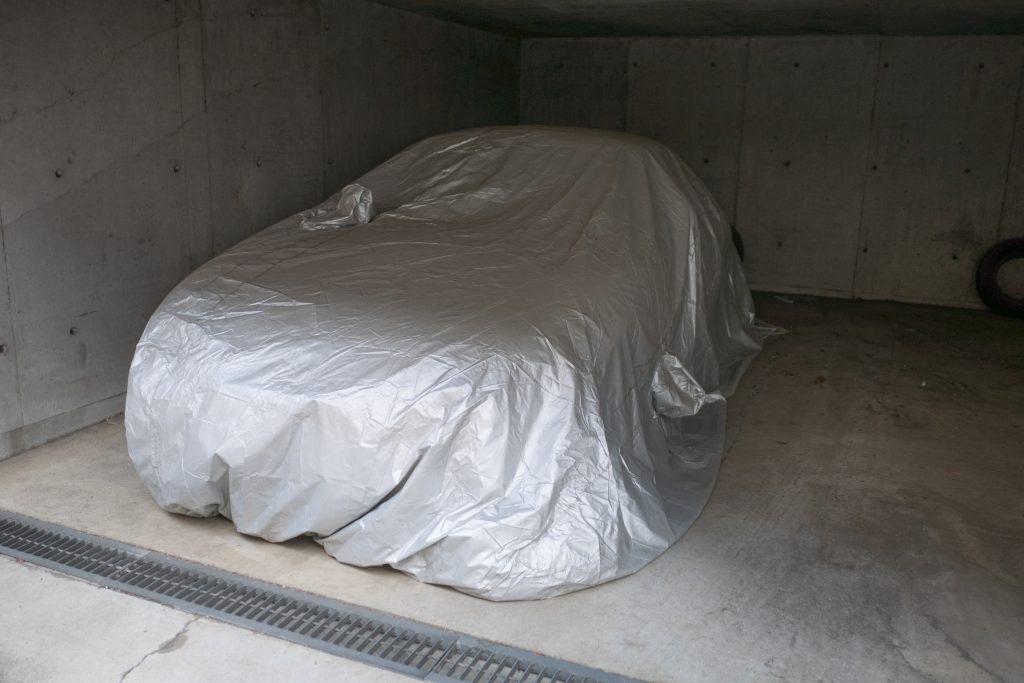tarp covered car in storage