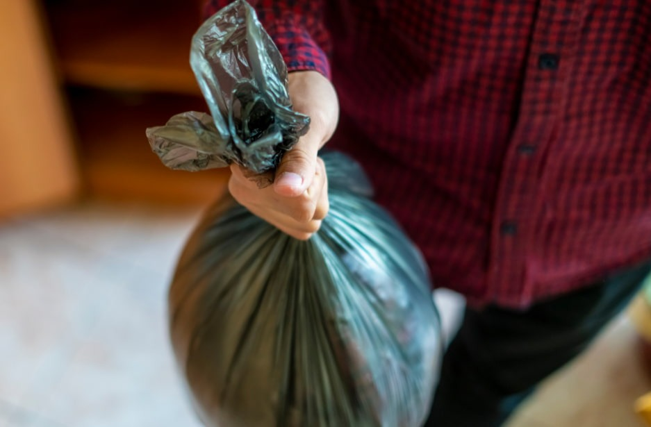 a person carries a trash bag which is being used for storage