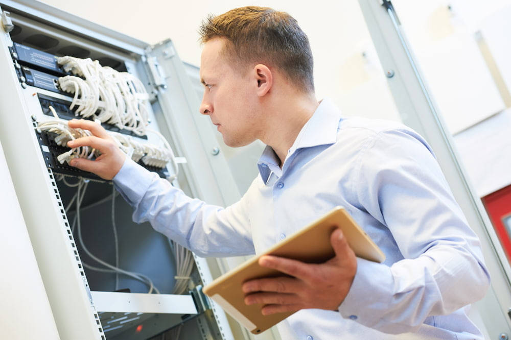 I.T. worker looking at electronical in an office preparing to move to a new location