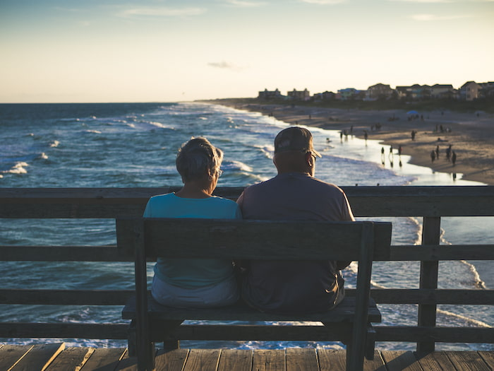 An elderly couple sits on a bench at Emerald Isle, NC.