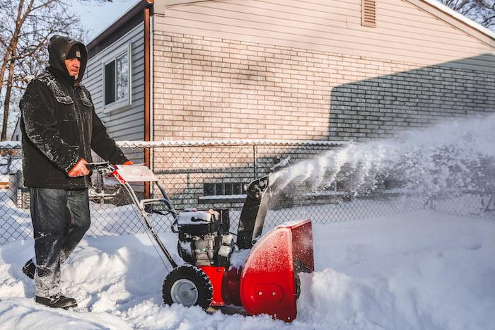 A man clears a driveway using a snowblower