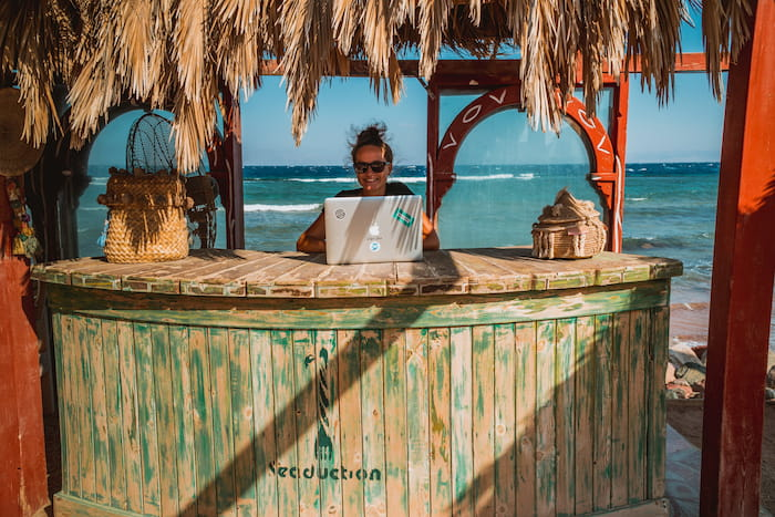 a digital nomad works from the beach