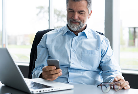 Man with a blue shirt looking at his phone sitting at his laptop